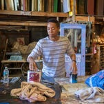 Lephate Cunningham III works on painting at the Barn Theatre.