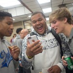 Dytarious Johnson, center, who intends on signing with Michigan, looks at his phone with friends Ricky Shuford, left, and Derek Gappa, right, during a signing day reception at Prattville High School on Wednesday, Feb. 3, 2016, in Prattville, Ala.
