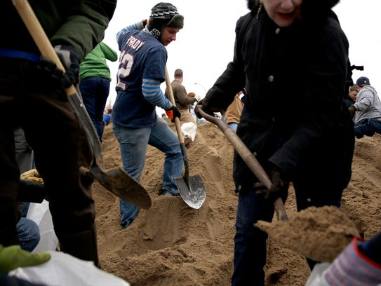Jason Fitzgibbons, center, helps fill sandbags with