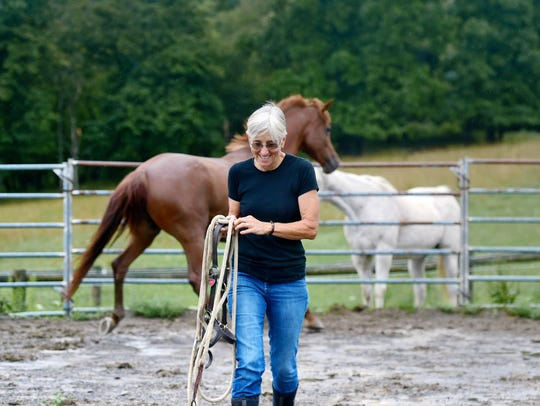 Pam Karner of Ithaca attends to her horses. The retired