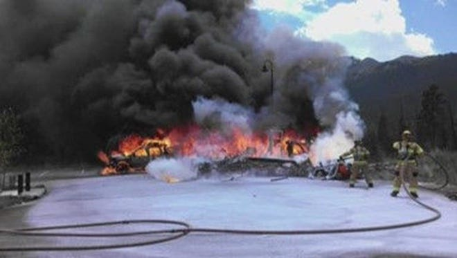 Firefighters battle the blaze July 3, 2015, at the crash of a Flight for Life helicopter in Frisco, Colo.