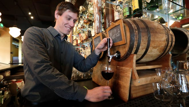 Jason Appleton pours a glass of wine from a small barrel at Luc's restaurant as he demonstrates that the same system could be used for consumers using their own growlers, in Seattle.