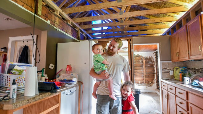 Zach Langloss stands with his two children Eliana, 3, and Avidan, 1, in the kitchen of the home he shares with his wife Danielle on Friday, July 31, 2020 in Creve Coeur. The home, which was undergoing extensive renovations, was severely damaged by rainstorms earlier in the month.