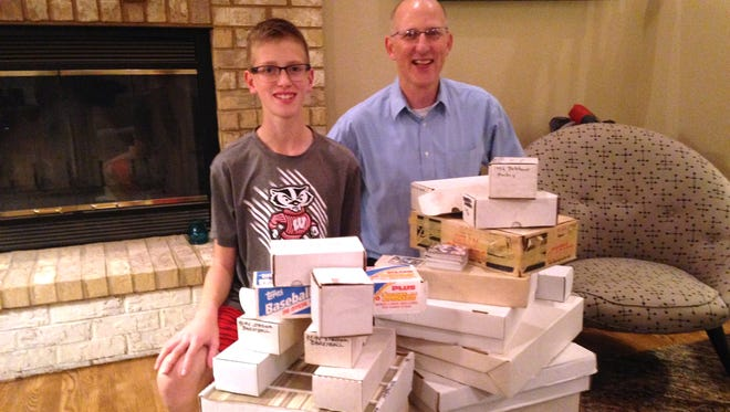Emmett Loew and his father, John, show off the many boxes of sports trading cards they received free of charge from a collector they met on Craigslist, Joe Durkatz.