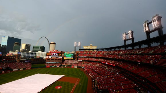 The St. Louis Cardinals grounds crew removes the tarp as a rainbow appears before a game June 15 against the Minnesota Twins at Busch Stadium.