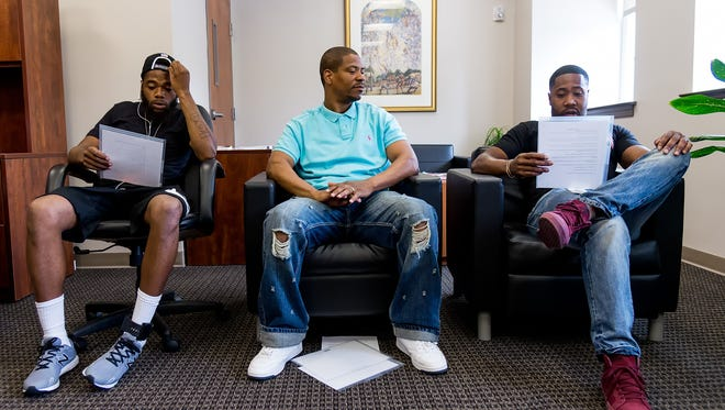 Corie Priest (center), an in-reach coordinator at Wilmington Hope Commission's Achievement Center, Kontal Copeland (right), a peer support specialist, participate in a support group for ex-offenders.