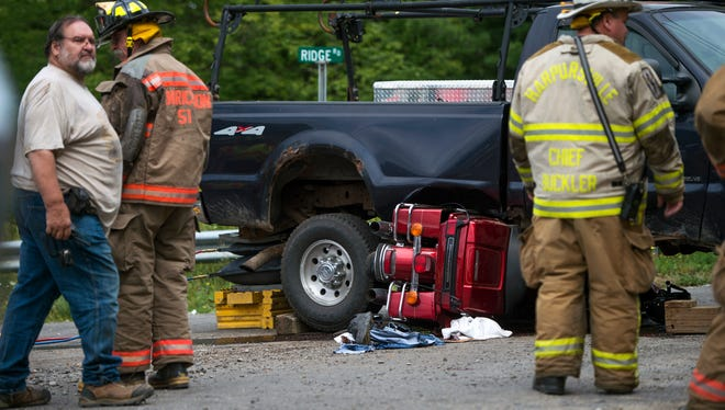 Emergency crews attend the scene of an accident where a motorcyclist was trapped beneath a pickup truck in Colesville on Thursday, August 27, 2015.