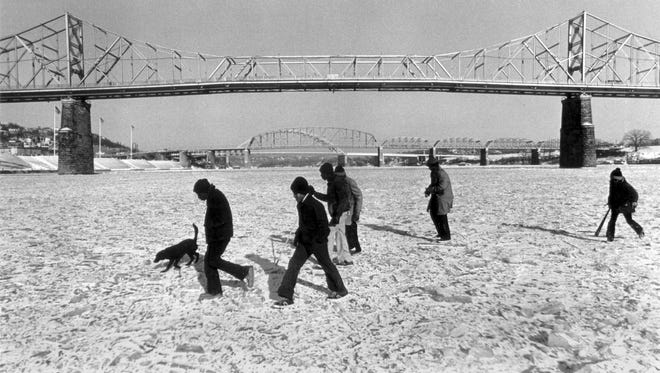 Kids dressed in jeans and sneakers walk carefully on the frozen Ohio River at the midpoint between Kentucky and Ohio near the Public Landing in January 1977.