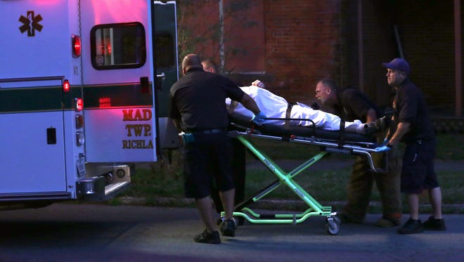 Madison Township paramedics transport a person who had an overdose to a hospital at the intersection of West First and Wood Street on Aug. 10, 2016. During that night there were nine overdoses in a 40 minute time span.