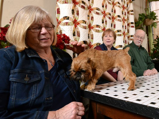 Evelyn Hole, left, pets Newton a Brussels Griffon Wednesday,