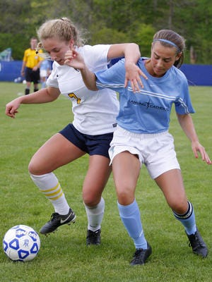 Dewitt's Danielle Stephan, left, and Lansing Catholic's Shannon Crilley battle for the ball Tuesday, May 17, 2016, in DeWitt, Mich. DeWitt won 2-0.