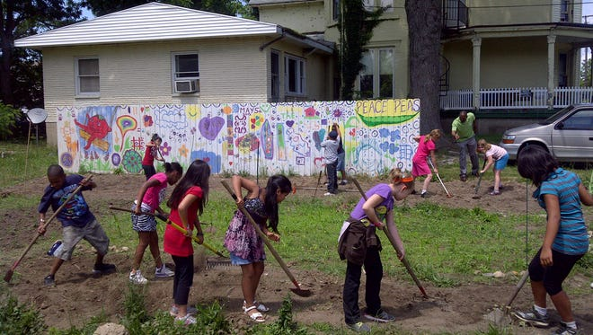 A group of kids works on the Fremont Garden.