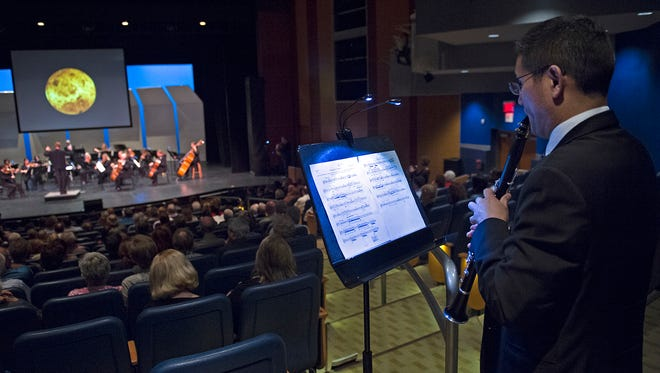 Eckart Preu leads the Cincinnati Chamber Orchestra with NASA images projected, while clarinetist John Kurokawa, foreground, performs a solo.