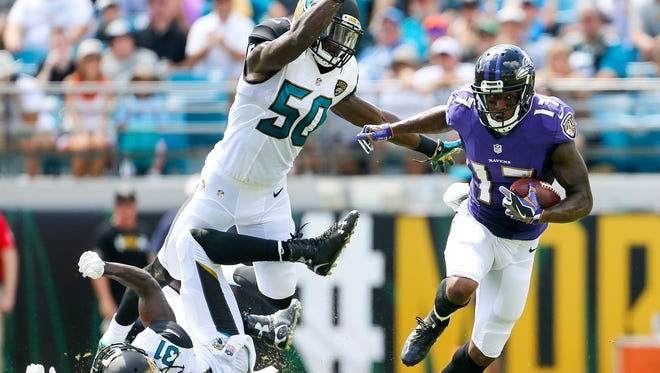 Baltimore Ravens wide receiver Mike Wallace (17) runs after a catch in the first quarter as Jacksonville Jaguars outside linebacker Telvin Smith (50) defends at EverBank Field. Baltimore Ravens won 19-17. Mandatory Credit: Logan Bowles-USA TODAY Sports