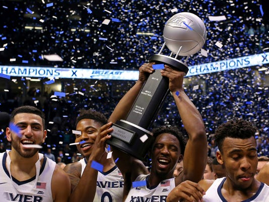 Xavier's Kerem Kanter, left, Tyrique Jones, middle, celebrate as Trevon Bluiett, right, holds up the Big East Trophy after clinching a share of the Big East title after an NCAA college basketball game against Providence, Wednesday, Feb. 28, 2018, in Cincinnati. Xavier won 84-74. (AP Photo/Aaron Doster)