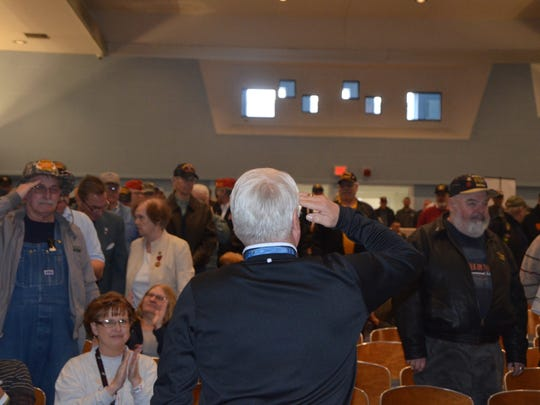 Medal of Honor recipient Jim McCloughan turns to the crowd to  salute his fellow veterans after veterans of the Vietnam War were asked to stand at the Battle Creek VA Medical Center on Thursday, March 29, 2018.