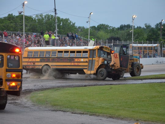 A forklift turns a bus upright as the sold-out crowd at Galesburg Speedway chanted 'Flip that bus' on Sunday, June 3, 2018.