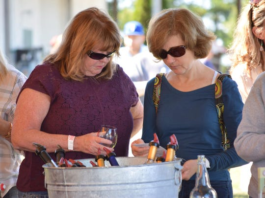 Lynda Giordano of Blackwood and Lori Belcher of Collingswood look over their wine list to pick out the next variety to taste during the Italian Festival at Bellview Winery.