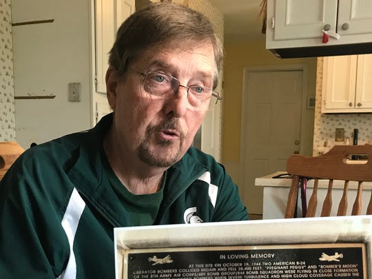 Dennis Lithander of Delta Township displays a photograph
