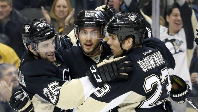 Jan. 27, 2015: Pittsburgh Penguins center Mark Arcobello (left) and defenseman Kris Letang (center) and right wing Steve Downie celebrate a goal by Downie against the Winnipeg Jets during the second period at the CONSOL Energy Center.