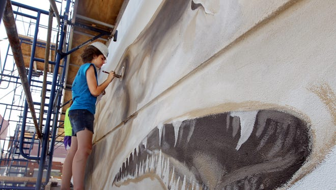 Eliora Kirk, of Liberty Township, works on the eye of a sand shark, part of a 300-foot-long mural being painted on the north wall of the Newport Aquarium to celebrate the aquarium's 15th birthday. Kirk is an apprentice with ArtWorks.