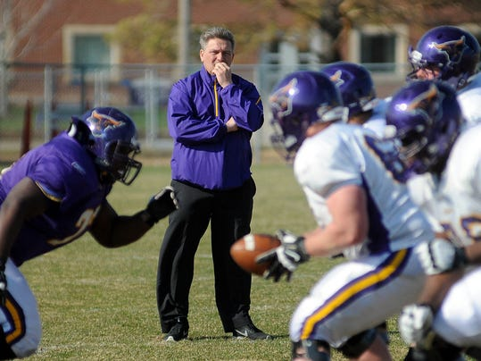 Minnesota State, Mankato football coach Todd Hoffner watches drills during the NCAA college football team's practice, Friday, April 18, 2014, in Mankato, Minn. It was Hoffner's first practice after an arbitrator ruled that Hoffner had been wrongly fired. Players had refused to suit up earlier in the week, in support of interim coach Aaron Keen. (AP Photo/Mankato Free Press, John Cross)