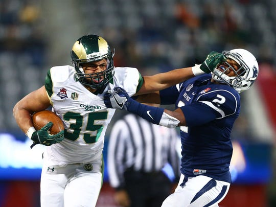 Dec 29, 2015; Tucson, AZ, USA; Colorado State Rams running back Izzy Matthews (35) stiff arms Nevada Wolf Pack defensive back Asauni Rufus (2) in the second half of the Arizona Bowl at Arizona Stadium. Nevada defeated Colorado State 28-23.  Mandatory Credit: Mark J. Rebilas-USA TODAY Sports