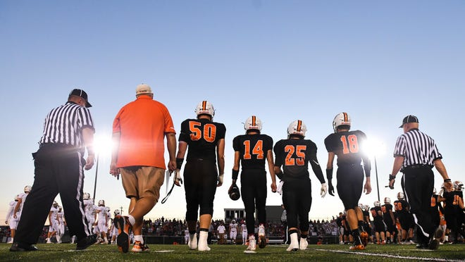 Washington players walk to the center of the field for the coin toss to start a 2018 Mid-Illini conference football game with Dunlap.