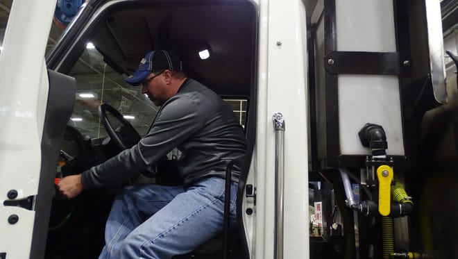 Jeromy Caskey, transportation manager for Marion County with the Ohio Department of Transportation, demonstrates how salt truck drivers should check their vehicles before heading out.