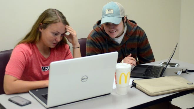 William Carey seniors Taylor Brewer, left, and Briana Bass work on class assignments in the library after classes started back at Carey. The Jan. 21 tornado damaged and destroyed many buildings on Carey's campus.