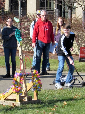 An engineering student launches a water balloon Monday at Corning Community College with a catapult his team designed.