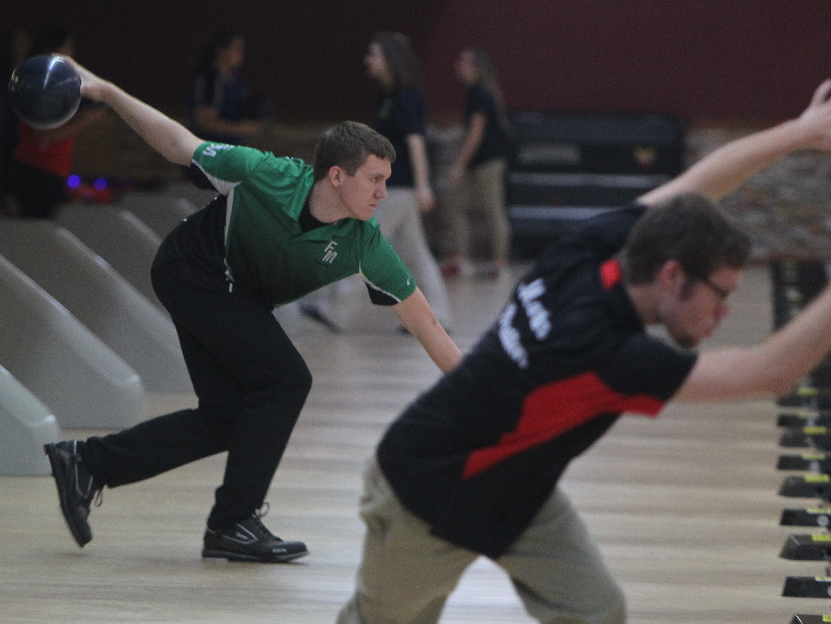 Fort Myers bowler Andrew Meece, left, hits a strike during District 6 bowling tournament Tuesday at Bowland in Cape Coral.