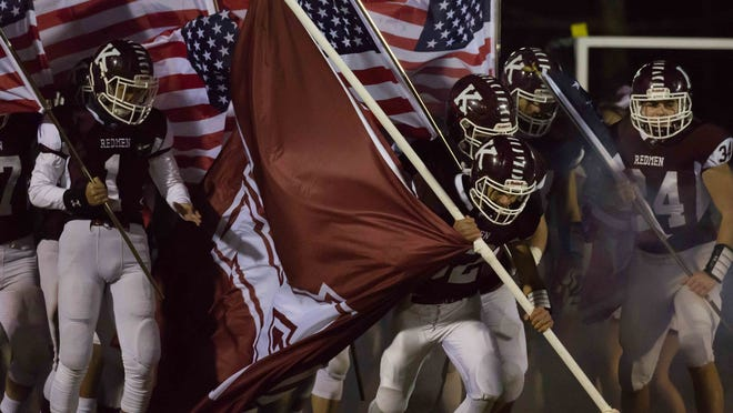 :Members of the Killingly football team take the field for a game last season.