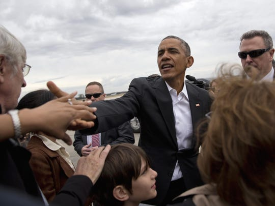 President Barack Obama greets people on the tarmac before boarding Air Force One at Baton Rouge Metropolitan Airport in Baton Rouge Thursday, en route to Washington after participating in a town hall at McKinley Senior High School.