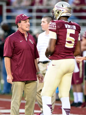 Florida State coach Jimbo Fisher and quarterback Jameis Winston (5) share an awkward moment Saturday night when Winston came out of the locker room in uniform despite being suspended from playing.