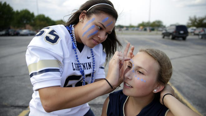 Emily Rohloff (right) has her face painted by Jada Taylor before an Appleton North football game in August.