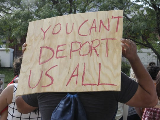"""A man holds a wooden sign that reads, """"You can't deport us all,"""" at a rally in support of Deferred Action for Childhood Arrivals at Riehle Plaza in Lafayette on Tuesday, Aug. 15, 2017."""