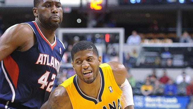 Paul George drives around Hawks defender Elton Brand. The Indiana Pacers hosted the Atlanta Hawks in NBA action Sunday April 6, 2014 at Bankers Life Fieldhouse.