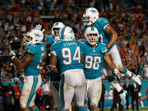 Miami Dolphins defensive end Cameron Wake (91) celebrates with defensive tackle Randy Starks (94) defensive tackle Jared Odrick (98) and safety Jimmy Wilson (27) after Wake's sack for a safety in overtime on Cincinnati Bengals quarterback Andy Dalton
