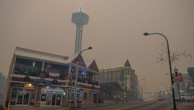 Thick smoke from area forest fires covers the Parkway in downtown Gatlinburg on Monday, Nov. 28, 2016.