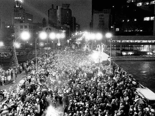 Crowds on downtown bridge celebrating New Year's Eve. There was a fireworks display to mark the end of the Sesquicentennial.