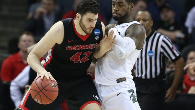 Michigan State's Branden Dawson defends against Georgia's Nemanja Djurisic during the second half action of Friday's win in Charlotte, N.C.