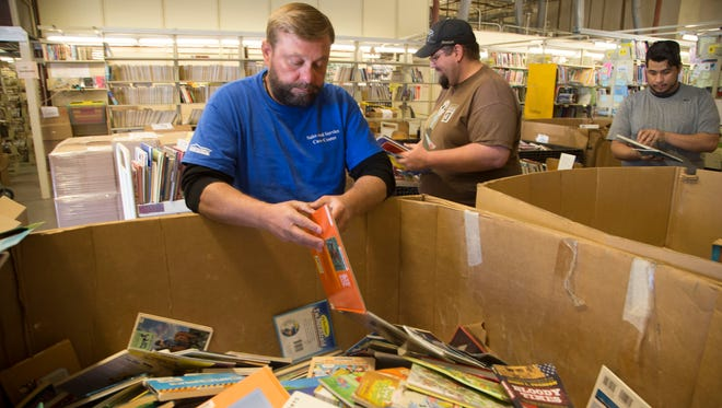Friends of the Phoenix Public Library volunteer Jeff Zieser sorts through donated books in Phoenix. In March, the non-profit launched the BookStorm program, which donates books to local schools and brings public library resources directly to the classroom.