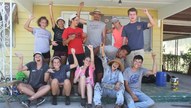 Mission Carlsbad volunteers celebrate after the last day of working. The project, which has helped repair about 20 homes in Carlsbad and Loving, ended Friday.