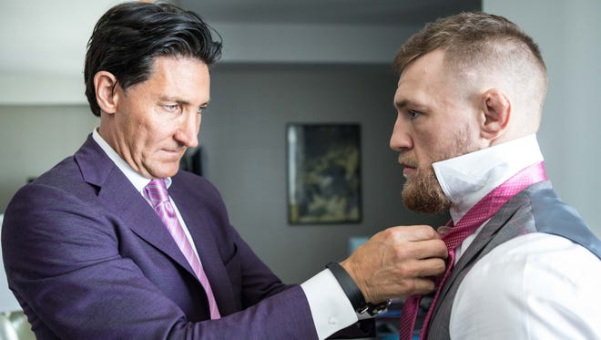 David August Heil, left, helps Conor McGregor with his tie in outfitting the fighter with one of his designer suits.