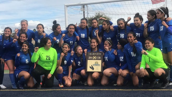 The Fillmore High girls soccer team poses with its championship plaque after beating Azusa 3-1 in the CIF-Southern Section Division 7 final Saturday at Warren High in Downey. The Flashes earned the program's first CIF title.