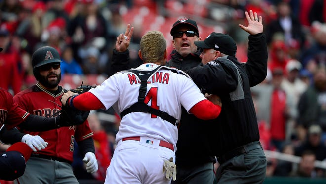 Arizona Diamondbacks manager Torey Lovullo (17) and St. Louis Cardinals catcher Yadier Molina (4) exchange words as umpire Tim Timmons (95) attempts to separate them during the second inning of an April game at Busch Stadium.