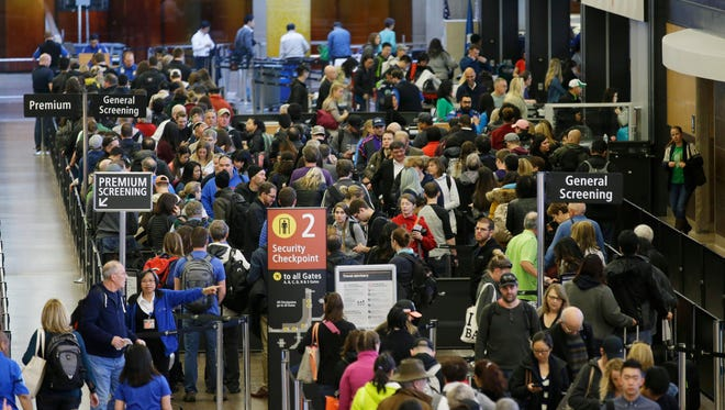 In this March 17, 2016, photo, travelers wait in line for security screening at Seattle-Tacoma International Airport.