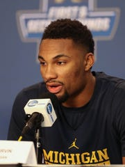 Michigan Wolverines guard Zak Irvin talks with reporters