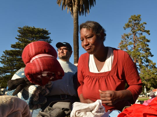 Sergio Chingon (left) and Denell Maria Biviens visit a table of clean clothes and blankets given away at the 11th Annual Homeless Persons' Memorial Service held Sunday at Plaza Park in Ventura.